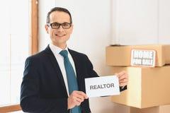 Pośrednika handlu nieruchomościami mienia pośrednik handlu nieruchomościami podpisuje wewnątrz nowego mieszkanie z kartonami Zdjęcie Stock