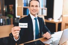 Pośrednika handlu nieruchomościami obsiadanie przy biurkiem w biurze Mężczyzna pozuje na kamerze z pośrednika handlu nieruchomośc Zdjęcie Royalty Free