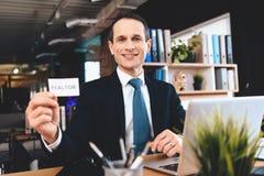 Pośrednika handlu nieruchomościami obsiadanie przy biurkiem w biurze Mężczyzna pozuje na kamerze z pośrednika handlu nieruchomośc Zdjęcia Stock