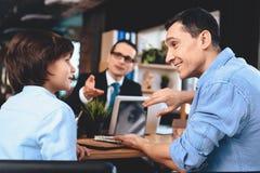 Pośrednika handlu nieruchomościami obsiadanie przy biurkiem w biurze Ojciec trzyma pastylkę pokazuje syn Zdjęcia Stock