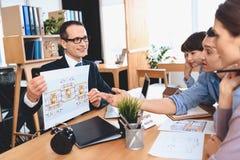 Pośrednika handlu nieruchomościami obsiadanie przy biurkiem w biurze Pośrednik handlu nieruchomościami pokazuje mieszkanie układ  Obraz Stock