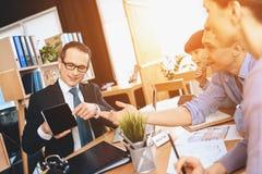 Pośrednika handlu nieruchomościami obsiadanie przy biurkiem w biurze Pośrednik handlu nieruchomościami pokazuje pastylkę ojciec,  Obraz Stock