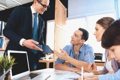 Pośrednika handlu nieruchomościami obsiadanie przy biurkiem w biurze Pośrednik handlu nieruchomościami pokazuje pastylkę ojciec,  Obraz Royalty Free