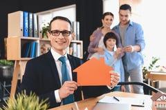 Pośrednika handlu nieruchomościami obsiadanie przy biurkiem w biurze Pośrednik handlu nieruchomościami przedstawia domową wycinan Obraz Royalty Free