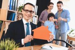 Pośrednika handlu nieruchomościami obsiadanie przy biurkiem w biurze Pośrednik handlu nieruchomościami przedstawia domową wycinan Zdjęcie Stock
