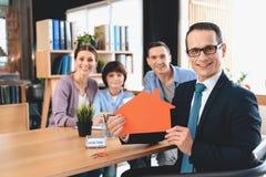 Pośrednika handlu nieruchomościami obsiadanie przy biurkiem w biurze Pośrednik handlu nieruchomościami przedstawia domową wycinan Obrazy Stock
