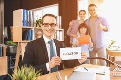 Pośrednika handlu nieruchomościami obsiadanie przy biurkiem w biurze Pośrednik handlu nieruchomościami przedstawia pośrednika han Obrazy Stock
