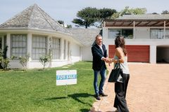 Pośrednika handlu nieruchomościami powitania klient na zewnątrz nowego domu dla sprzedaży Zdjęcie Stock