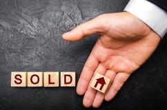 pośrednika handlu nieruchomościami ` s ręka stawia sześcian z obrazkiem dom słowo sprzedający Pojęcie sprzedawać dom, mieszkanie, fotografia royalty free