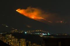 Pożar lasu w górach nad miasto, płomienie obok hous obraz stock