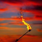 Pożarnicza pochodnia przy zmierzchu niebem z czerwonymi chmurami obrazy stock