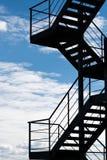 Pożarnicza ucieczka lub zewnętrznie schody na budynku sylwetkowym przeciw jaskrawemu niebu obrazy royalty free