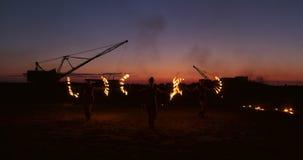 Pożarnicze przedstawienia trzy kobiety w ich rękach przekręcają płonące dzidy i fan w piasku z mężczyzną z dwa miotacz ognia w wo zbiory