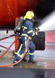 Pożarniczego wojownika boju ogień z wężem elastycznym fotografia royalty free