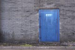 Pożarniczego wyjścia utrzymania jasnego znak na fabryce na zewnątrz drzwiowej błękitnej czerwieni i cieni popielaty Zdjęcia Royalty Free