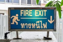 Pożarniczego wyjścia znak który zawartość w Tajlandzkim i Angielskim Obrazy Stock
