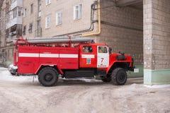 Pożarniczej usługa samochód opuszcza od jarda multistory budynek po wezwania Obraz Stock