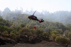 Pożarniczy śmigłowcowy lata nad palącą ziemią Obraz Royalty Free