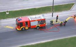 Pożarniczy świder z cztery mężczyzna który walczy z ogieniem Zdjęcie Royalty Free