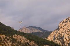Pożarniczy helikopter z pełnym koszem woda lata gasić pożar lasu przeciw tłu góry fotografia royalty free