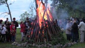 Pożarniczy płomień w ogromnym pożarniczym miejscu i ludzie grżemy blisko go zbiory