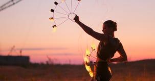 Pożarniczy tancerze przeciw zmierzchowi Młodej kobiety pozy z ona pożarniczy obręcz przeciw zmierzchowi podczas jej tana występu zbiory