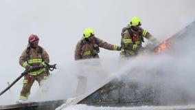 Pożarniczy wojownicy stoją i chodzą na dachu budynek mieszkaniowy zbiory