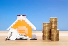 Pożyczki dla nieruchomości pojęcia Wzorcowy dom z kluczem i monetami Fotografia Stock