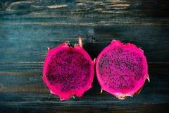 Połówka czerwona smok owoc na drewnianym tle Obrazy Stock