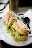 Po Boy Sandwich. A foot long Po Boy submarine sandwich on a plate with a knife and fork Stock Photo