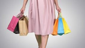 Po dnia zakupy młodej kobiety przewożenia toreb na zakupy podczas gdy chodzący na gradientowym tle zbiory wideo