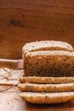 Pão integral inteiro cortado na placa de corte Imagens de Stock Royalty Free