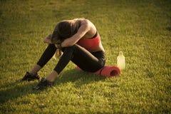 Po treningu Zmęczona kobieta w sportswear relaksuje po treningu, trenuje zdjęcia stock