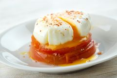 Poached egg. Above cooked tomato slices on dish Stock Photo
