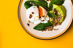 Poached egg with avocado cream and spinach on the yellow background top view Stock Photo