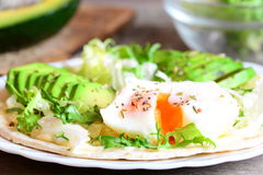Poached egg, avocado slices, salad mix, chinese cabbage, dried herbs, sauce on a tortilla. Delicious tortilla with filling Royalty Free Stock Photos