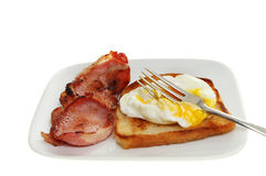 Poached egg and bacon. Poached egg with a fork resting in runny yolk with fried bread and bacon on a plate isolated against white Royalty Free Stock Image
