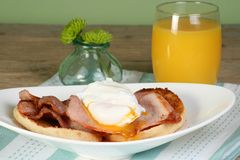 Poached egg and bacon. On a toasted english muffin with orange juice Stock Photos