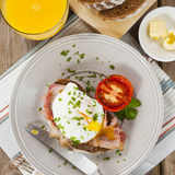 Poached egg and bacon on rye bread, healthy breakfast Royalty Free Stock Photography