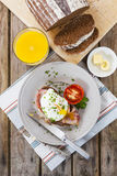 Poached egg and bacon on rye bread, healthy breakfast Stock Image