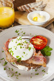 Poached egg and bacon on rye bread, healthy breakfast Stock Photo