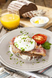 Poached egg and bacon on rye bread, healthy breakfast Royalty Free Stock Photo