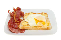 Poached egg bacon. Poached egg on toast with runny yolk and crispy bacon on a plate isolated against white Stock Images