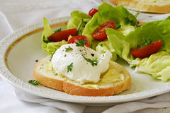 Poached egg on baguette slice with salad and tomatoes on a white Royalty Free Stock Photo