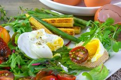 Poached egg with corn vegetables, grilled pepper, spinach, arugula, green beans and baby salad. Close up. Natural food stock photos