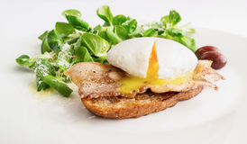 Poached egg on fried toast with bacon, olives, and green salad sprinkled with parmesan Stock Photos