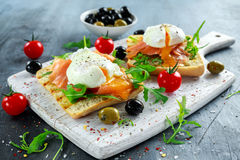 Poached egg on grilled toast with smoked salmon, rucola, olives and vegetables on white board. healthy breakfast.  Royalty Free Stock Images