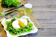 Poached egg, lettuce leaves with pomegranate seeds and olive oil. Healthy salad on a plate, fork, knife on old wooden background Royalty Free Stock Photo