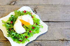 Poached egg, lettuce leaves with pomegranate seeds and olive oil. Healthy salad on a plate on wooden background Royalty Free Stock Photo