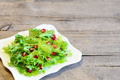 Poached egg, lettuce leaves with pomegranate seeds and olive oil. Healthy salad on a plate on wooden background Royalty Free Stock Photos